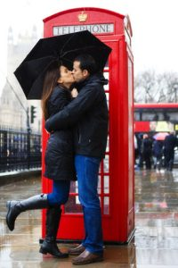 Couple of young tourist kissing in London under an umbrella. She is lifting her leg in a cute way.